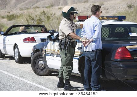 Middle aged policeman arresting a man