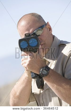 Portrait of a middle aged traffic officer looking through radar gun
