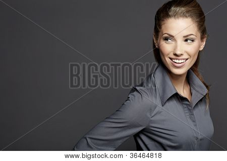 Portrait of a beautiful young business woman standing against grey background
