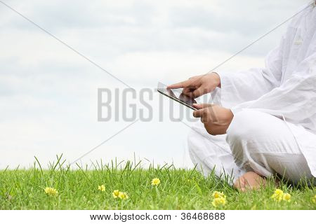 Man holding tablet pc on meadow