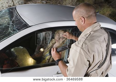 Middle aged policeman knocking car window