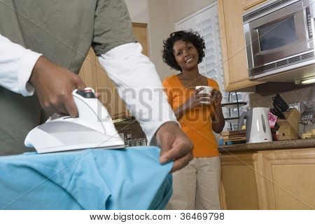 Woman Watching How Man Ironing His Shirt