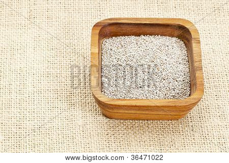 white chia seeds in square wooden bowl against burlap canvas