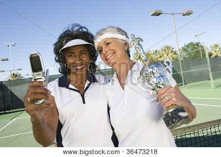 Happy senior women with trophy taking self-portrait through cell phone on tennis court
