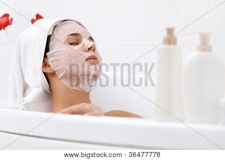Image of serene woman with facial mask enjoying bath in spa salon