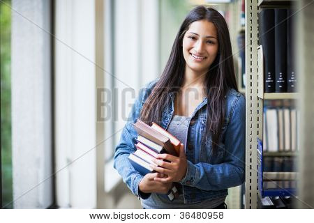 A portrait of an Hispanic college student in the library