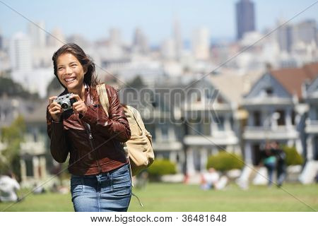 Alamo Square San Francisco Tourist. Young traveler woman holding camera in Alamo Park by the Painted Ladies, Seven Sisters, San Francisco, California, USA. Beautiful happy smiling multicultural woman