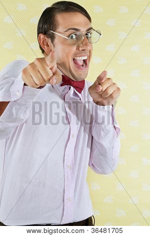 Portrait of an excited young geek with mouth open pointing at you over yellow textured background
