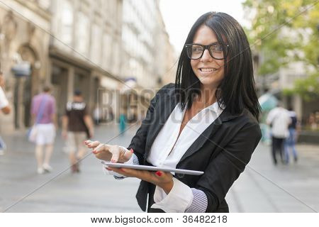 Beautiful Woman Using Tablet Computer on street, urban scene, formal clothing