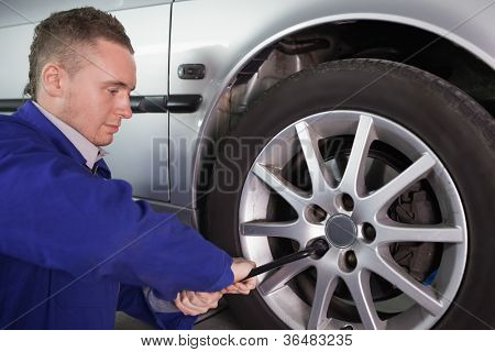 Man repairing a car wheel in a garage