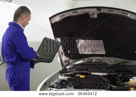 Man typing on a computer next to a car in a garage
