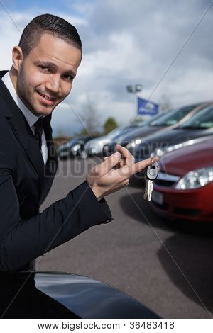 Man holding car keys with a finger outdoors