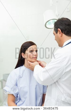 Doctor touching the neck of a patient in an examination room