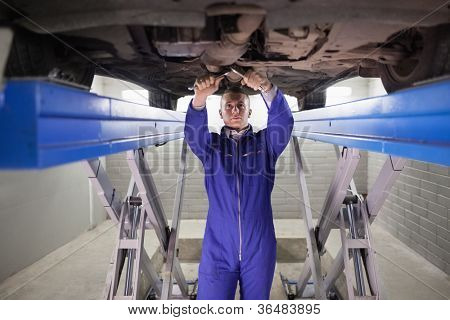 Mechanic repairing a car with tools in a garage