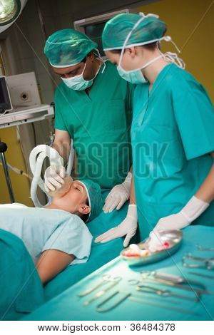 Surgeon working on a patient with a trolley with tools beside them in a surgical room