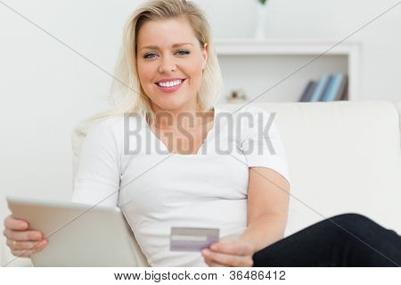 Casual woman with tablet pc and a credit card in a living room
