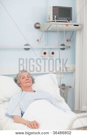 Elderly patient lying with closed eyes in hospital ward