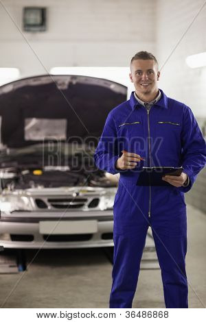 Mechanic holding a clipboard next to a car in a garage