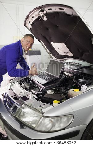 Mechanic repairing a car with a computer in a garage