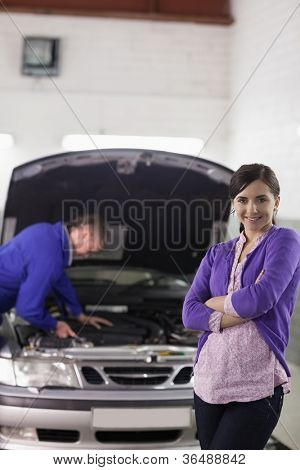 Client looking at camera with arms crossed in a garage