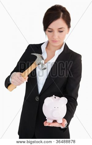 Woman in suit going to break a piggy-bank with a hammer against white background