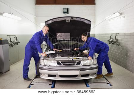 Mechanics leaning on a car looking at camera in a garage