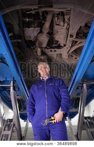 Mechanic standing up below a car in a garage