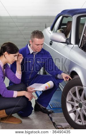 Mechanic touching the car wheel while looking at it in a garage