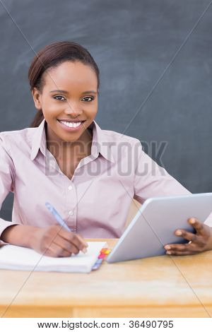 Teacher writing while using a tablet computer in a classroom