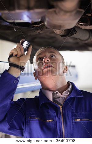 Mechanic holding a flashlight while looking at a car in a garage