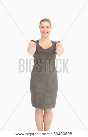 Woman standing while she is thumps up against white background