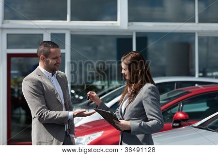 Businesswoman giving car keys to a client in a dealership