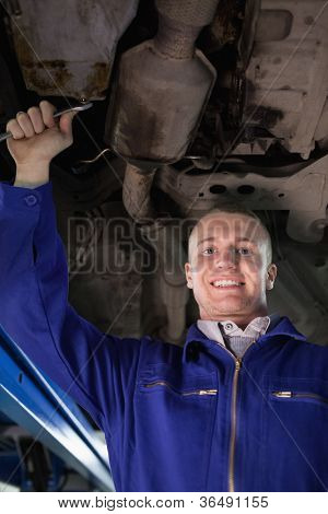 Smiling mechanic looking at camera below a car in a garage