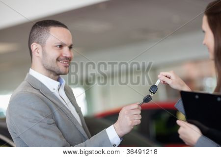 Businesswoman and man holding car keys in a garage