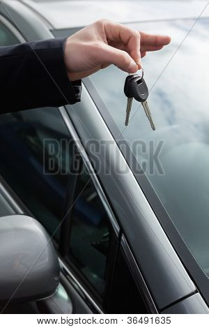 Someone holding car keys by his fingertips outdoors