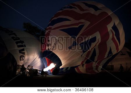 NORTHAMPTON, ENGLAND - AUGUST 18: Hot Air Balloons inflating at night  at the Northampton Balloon Festival, on August 18, 2012 in Northampton, England.