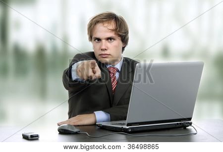young man pointing wile working with laptop