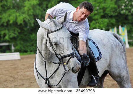 Jockey seat on horse feed from hand on hippodrome
