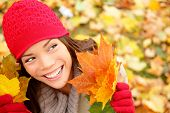 foto of knitted cap  - Fall woman looking at copy space holding fall leaves smiling happy and joyful - JPG