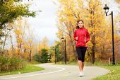 Running in Fall. Runner woman jogging in autumn forest. Beautiful young fit fitness sport model jogg