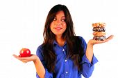 Young Woman Deciding Betwen Apple Or Donuts