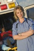 Portrait of a confident female EMT doctor standing with patient lying on stretcher in the background