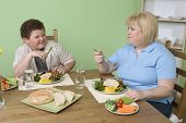 picture of obesity children  - Obese mother and son having meal together at home - JPG