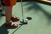 stock photo of miniature golf  - Putting a ball into a hole of crazy golf - JPG