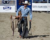 SAN JUAN CAPISTRANO, CA - AUGUST 25: unidentified cowboy carries his saddle in the ring at the PRCA