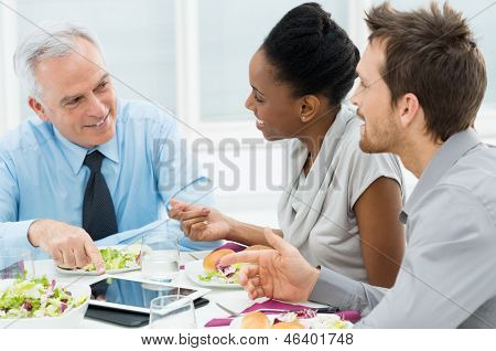 Business Colleagues Eating Meal Together While Discussing of Work
