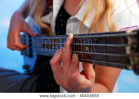 Young Girl Playing Bass Guitar On The Stage