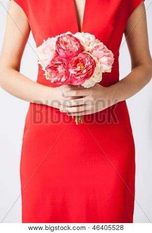 close up of woman hands with bouquet of flowers.