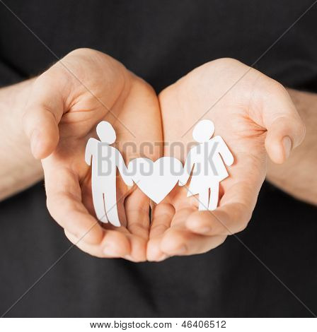 man hands showing two paper men with heart shape