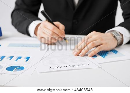 picture of man in suit signing contract